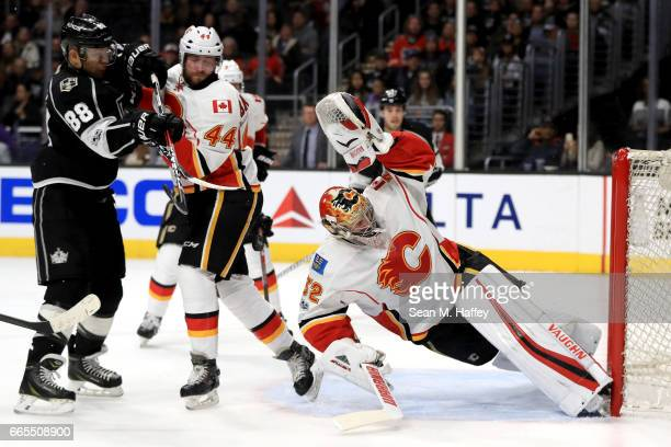 Jon Gillies as Matt Bartkowski of the Calgary Flames defends against Jarome Iginla of the Los Angeles Kings leaps to block a shot on goal during the...