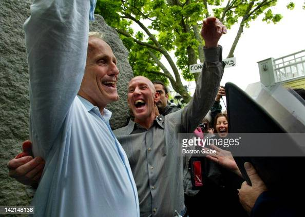 Jon Goode and Cary Raymond of Provincetown and the South End raise their hands after becoming the first couple to be married outside Town Hall