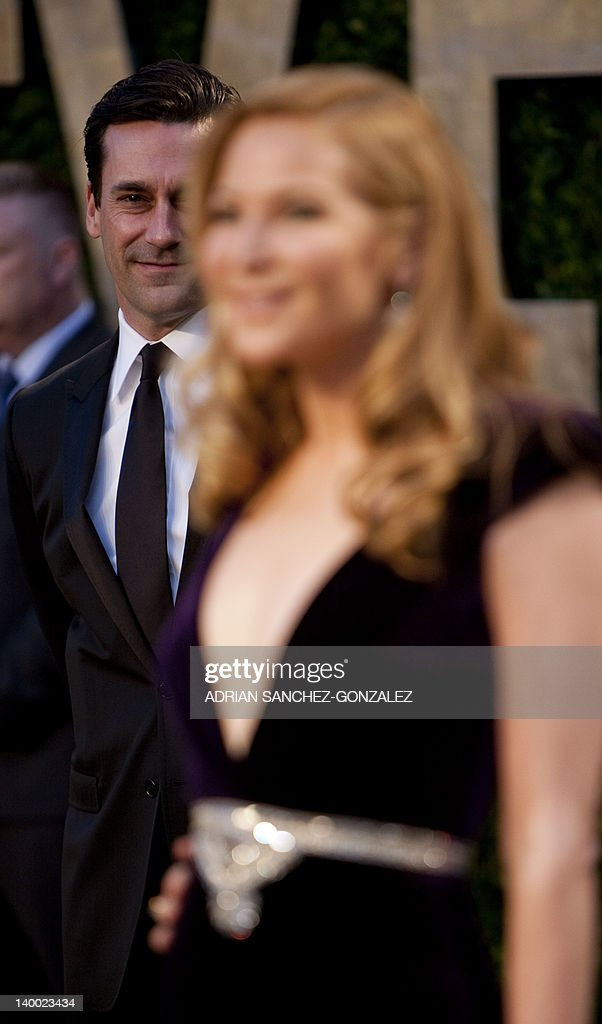 Jon Hamm (L) watches Jennifer Westfeldt have her photo taken on the carpet as they arrive at the Vanity Fair Oscar Party, for the 84th Annual Academy Awards, at the Sunset Tower on February 26, 2012 in West Hollywood, California.