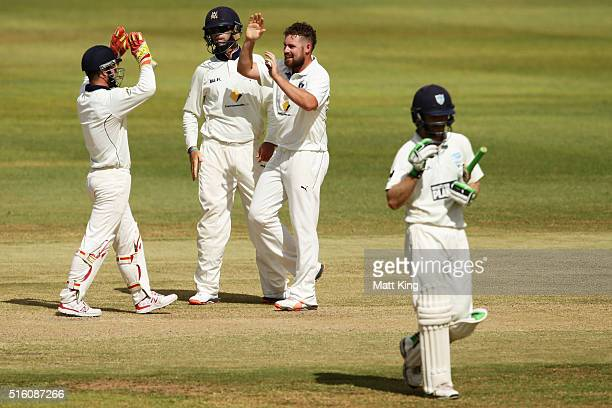 Jon Holland of the Bushrangers celebrates with team mates after taking the wicket of Ryan Carters of the Blues during day three of the Sheffield...