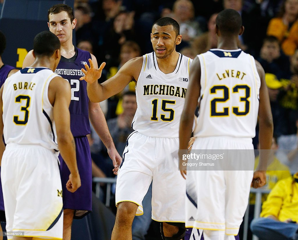 Jon Horford #15 of the Michigan Wolverines celebrates a second half basket with Caris LeVert #23 and Trey Burke #3 while playing the Northwestern Wildcats at Crisler Center on January 30, 2013 in Ann Arbor, Michigan. Michigan won the game 68-46.