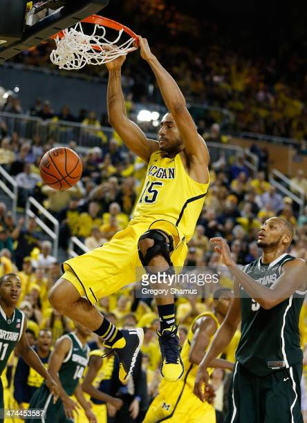 Jon Horford of the Michigan Wolverines gets in for a second half dunk in front of Adreian Payne of the Michigan State Spartans at Crisler Center on...