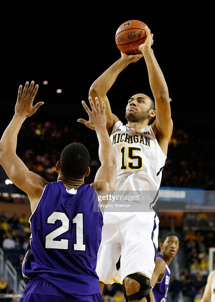 Jon Horford #15 of the Michigan Wolverines takes a first-half shot over Malachi Alexander #21 of the Holy Cross Crusaders at Crisler Center on December 28, 2013 in Ann Arbor, Michigan.