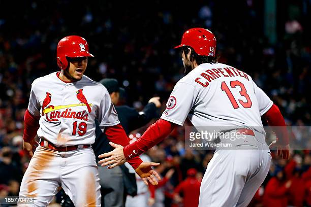 Jon Jay and Matt Carpenter of the St Louis Cardinals celebrate scoring in the seventh inning against the Boston Red Sox during Game Two of the 2013...