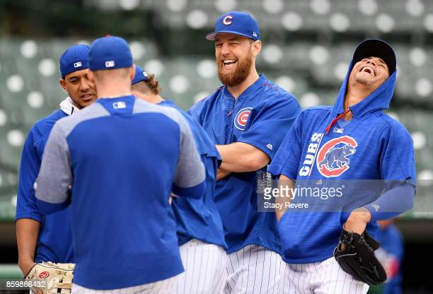 Jon Jay Ben Zobrist and Albert Almora Jr #5 of the Chicago Cubs meet before game four of the National League Division Series against the Washington...
