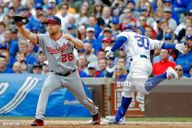 Jon Jay of the Chicago Cubs beats the throw as Adam Lind of the Washington Nationals takes the throw during the seventh inning at Wrigley Field on...