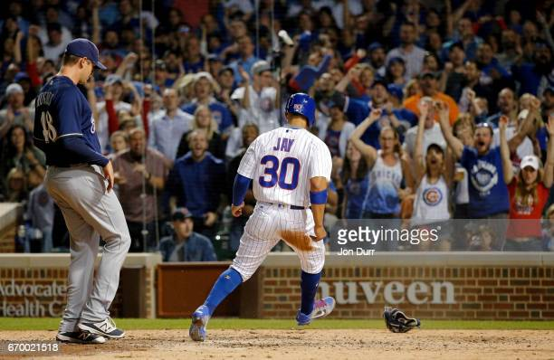 Jon Jay of the Chicago Cubs scores on a wild pitch by Jared Hughes of the Milwaukee Brewers during the sixth inning at Wrigley Field on April 18 2017...