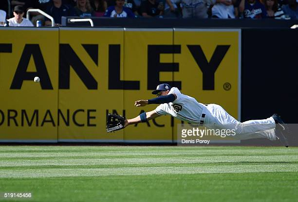 Jon Jay of the San Diego Padres dives but is unable to make the catch on a double hit by Chase Utley of the Los Angeles Dodgers during the first...