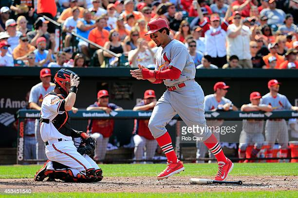 Jon Jay of the St Louis Cardinals celebrates after scoring a run in the fifth inning as catcher Caleb Joseph of the Baltimore Orioles looks on at...