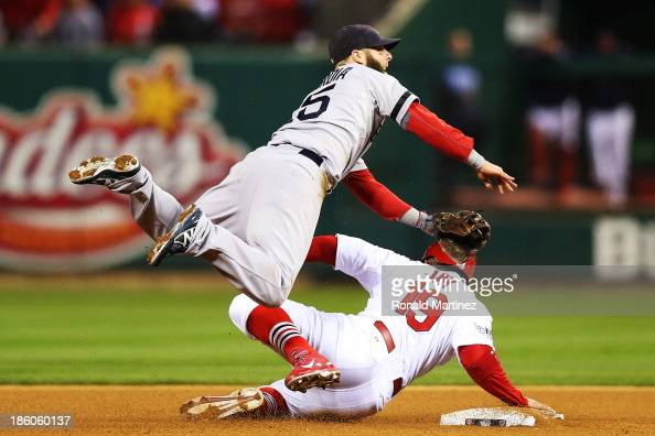 Jon Jay of the St Louis Cardinals gets tagged out at second base by Dustin Pedroia of the Boston Red Sox after David Freese hit grounder into...