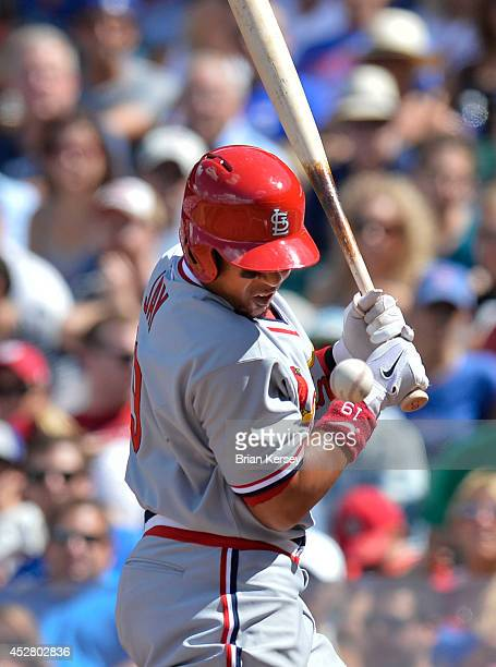 Jon Jay of the St Louis Cardinals is hit by a pitch during the seventh inning against the Chicago Cubs at Wrigley Field on July 27 2014 in Chicago...
