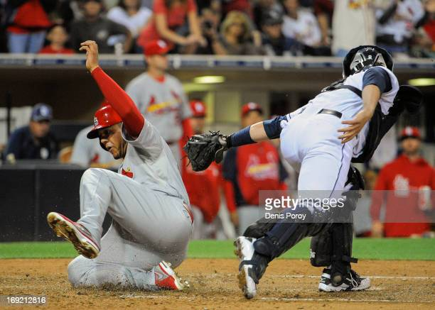 Jon Jay of the St Louis Cardinals scores ahead of the tag of John Baker of the San Diego Padres during the fifth inning of a baseball game at Petco...