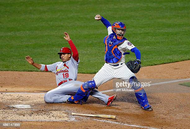 Jon Jay of the St Louis Cardinals slides into Travis d'Arnaud of the New York Mets as he attempts a fourth inning double play by throwing to first...