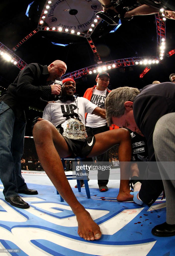 <a gi-track='captionPersonalityLinkClicked' href=/galleries/search?phrase=Jon+Jones+-+Mixed+Martial+Artist&family=editorial&specificpeople=8928306 ng-click='$event.stopPropagation()'>Jon Jones</a> (C) has his broken toe tended to while he is interviewed by <a gi-track='captionPersonalityLinkClicked' href=/galleries/search?phrase=Joe+Rogan&family=editorial&specificpeople=206681 ng-click='$event.stopPropagation()'>Joe Rogan</a> (R) after winning by knockout in round one against Chael Sonnen in their light heavyweight championship bout during the UFC 159 event at the Prudential Center on April 27, 2013 in Newark, New Jersey.