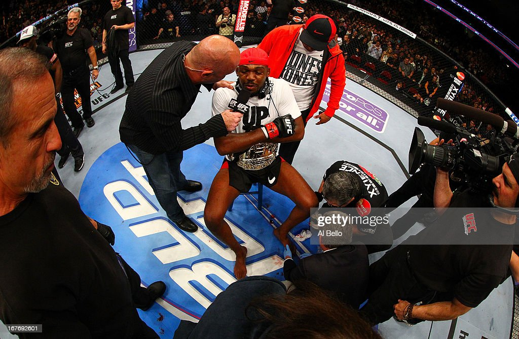 Jon Jones (C) has his broken toe tended to while he is interviewed by Joe Rogan (R) after winning by knockout in round one against Chael Sonnen in their light heavyweight championship bout during the UFC 159 event at the Prudential Center on April 27, 2013 in Newark, New Jersey.