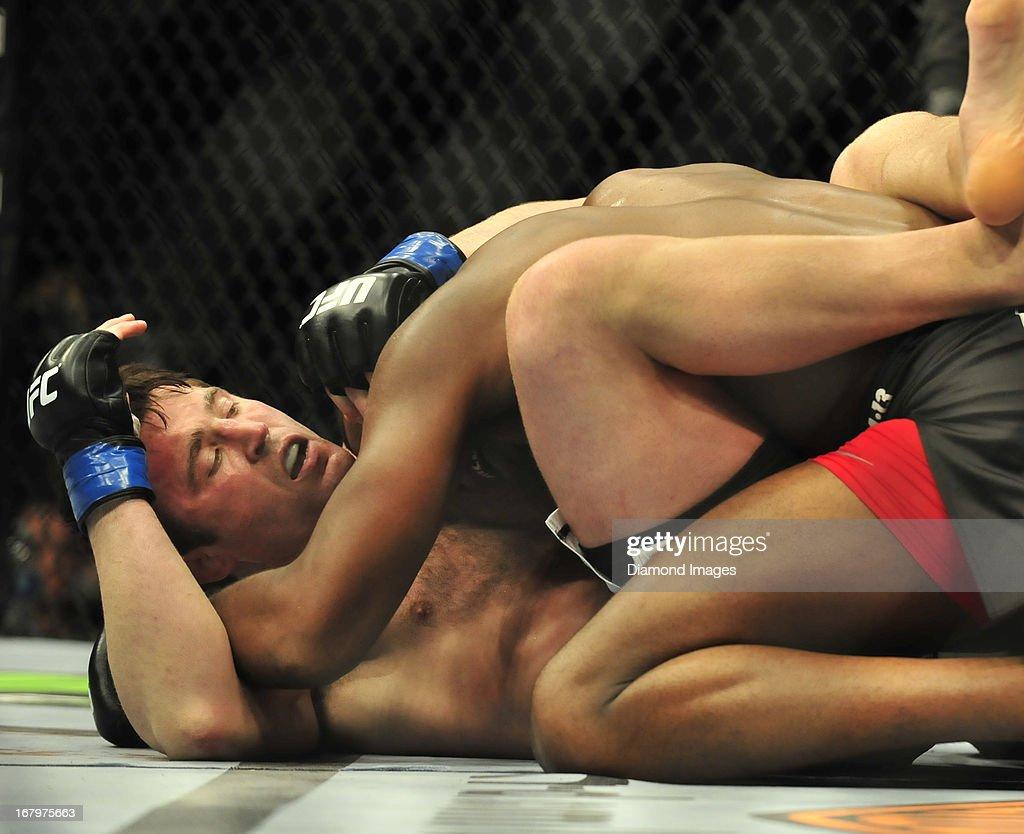 Jon Jones wrestles with Chael Sonnen on the mat during a light-heavyweight bout during UFC 159 Jones v. Sonnen at Prudential Center in Newark, New Jersey.