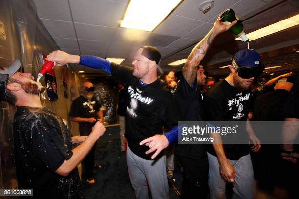Jon Lester and Ben Zobrist of the Chicago Cubs celebrate with teammates in the clubhouse after winning Game 5 of the National League Division Series...