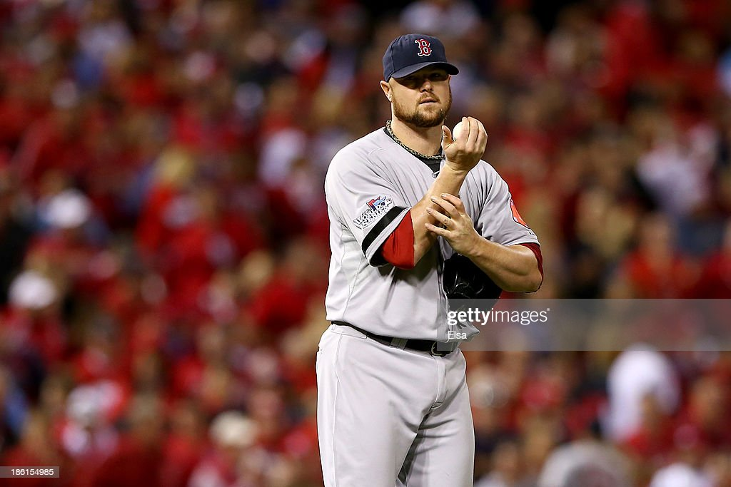 Jon Lester #31 of the Boston Red Sox holds his arm as he is removed from the game in the eighth inning of Game Five of the 2013 World Series against the St. Louis Cardinals at Busch Stadium on October 28, 2013 in St Louis, Missouri.