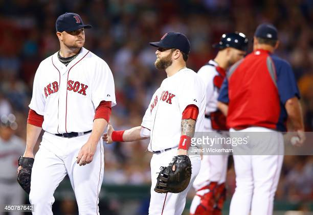Jon Lester of the Boston Red Sox is congratulated by teammate Mike Napoli after being pulled from the game in the seventh inning against the...