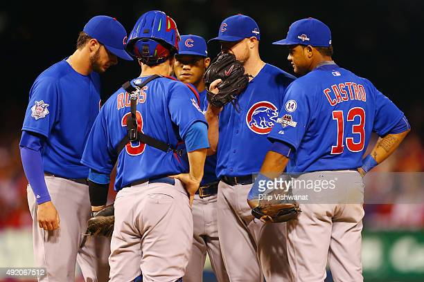 Jon Lester of the Chicago Cubs meets with members of the Chicago Cubs infield in the fourth inning during game one of the National League Division...