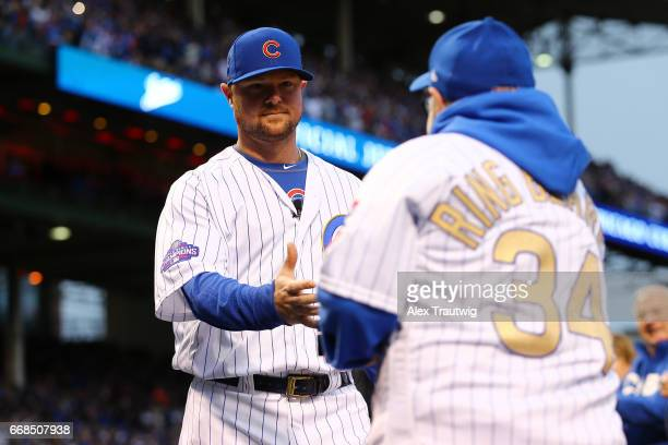 Jon Lester of the Chicago Cubs receives his ring from a fan during the World Series ring ceremony ahead of the game between the Los Angeles Dodgers...