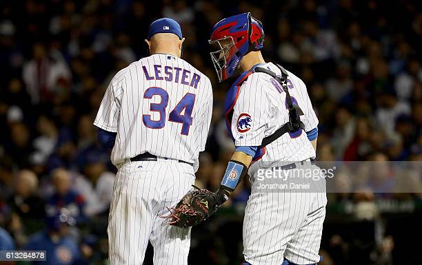 Jon Lester of the Chicago Cubs talks with David Ross in the fifth inning against the San Francisco Giants at Wrigley Field on October 7 2016 in...