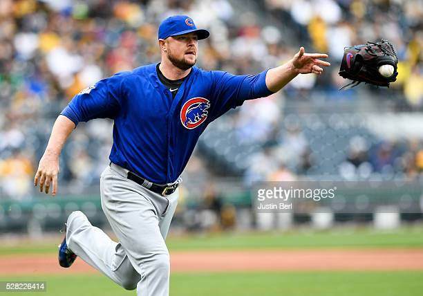 Jon Lester of the Chicago Cubs tosses his glove with the ball for a putout of Francisco Cervelli of the Pittsburgh Pirates at first base in the...
