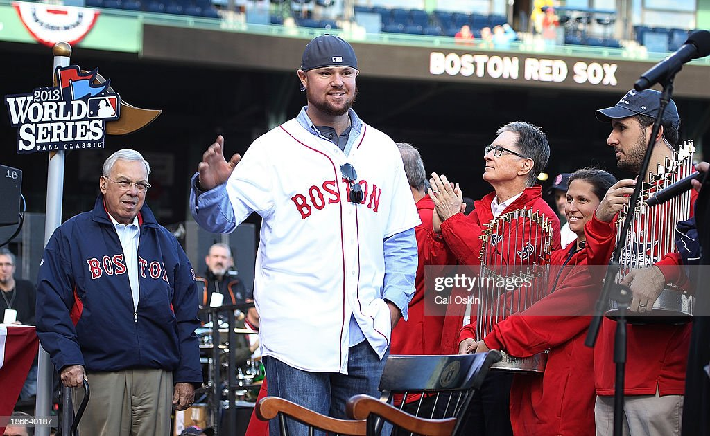 Jon Lester (center) walks on stage as Red Sox principal own John Henry (right) claps at Fenway Park before the Red Sox players board the duck boats for the World Series victory parade for the Boston Red Sox on November 2, 2013 in Boston, Massachusetts.