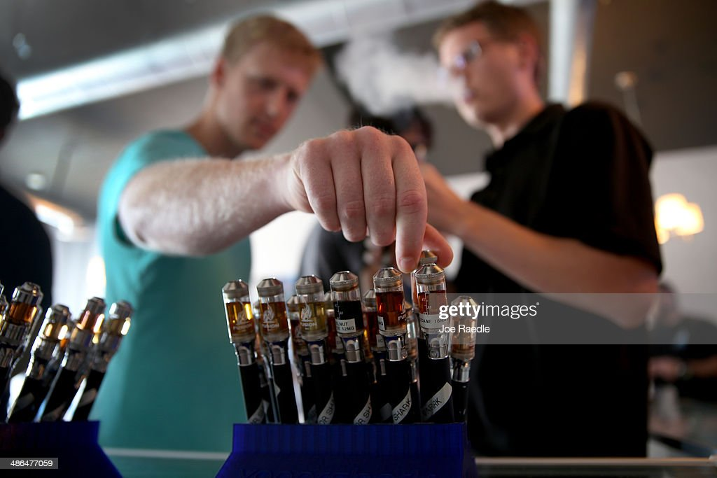 Jon Lusher (L) and Bret Wagner try different flavors of electronic cigarette vapor as they shop at the Vapor Shark store on April 24, 2014 in Miami, Florida. Brandon Leidel, CEO, Director of Operations Vapor Shark, said he welcomes the annoucement by the Food and Drug Administration that they are proposing the first federal regulations on electronic cigarettes, which would ban sales of the popular devices to anyone under 18 and require makers to gain FDA approval for their products.