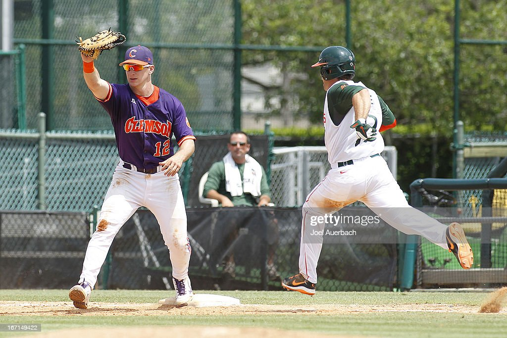Jon McGibbon #12 of the Clemson Tigers catches the ball getting Tyler Palmer #9 of the Miami Hurricanes out on April 21, 2013 at Alex Rodriguez Park at Mark Light Field in Coral Gables, Florida. Miami defeated Clemson 7-0.
