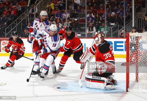 Jon Merrill and Cory Schneider of the New Jersey Devils defend against JT Miller of the New York Rangers during the first period at the Prudential...