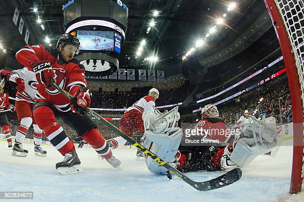 Jon Merrill and Keith Kinkaid of the New Jersey Devils defend the net against the Carolina Hurricanes at the Prudential Center on December 29 2015 in...
