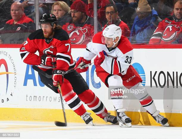 Jon Merrill of the New Jersey Devils and Derek Ryan of the Carolina Hurricanes battle for position during the game at Prudential Center on March 25...