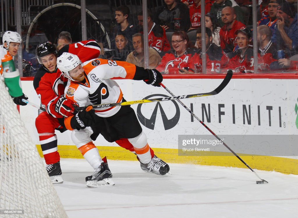 Jon Merrill #7 of the New Jersey Devils holds onto Claude Giroux #28 of the Philadelphia Flyers during the first period at the Prudential Center on April 4, 2017 in Newark, New Jersey.