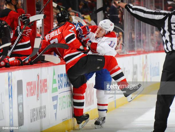 Jon Merrill of the New Jersey Devils is checked into the boards by Brendan Gallagher of the Montreal Canadiens during the first period at the...
