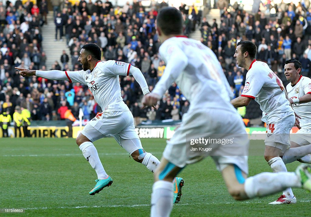 Jon Otsemobor of MK Dons (L) celebrates as he scores their second goal during the FA Cup with Budweiser Second Round match between MK Dons and AFC Wimbledon at StadiumMK on December 2, 2012 in Milton Keynes, England. This match is the first meeting between the two teams following the formation of AFC Wimbledon (the football club formed in 2002 by supporters unhappy with their club's relocation to Milton Keynes) and the MK Dons (which Wimbledon F.C. controversially became).