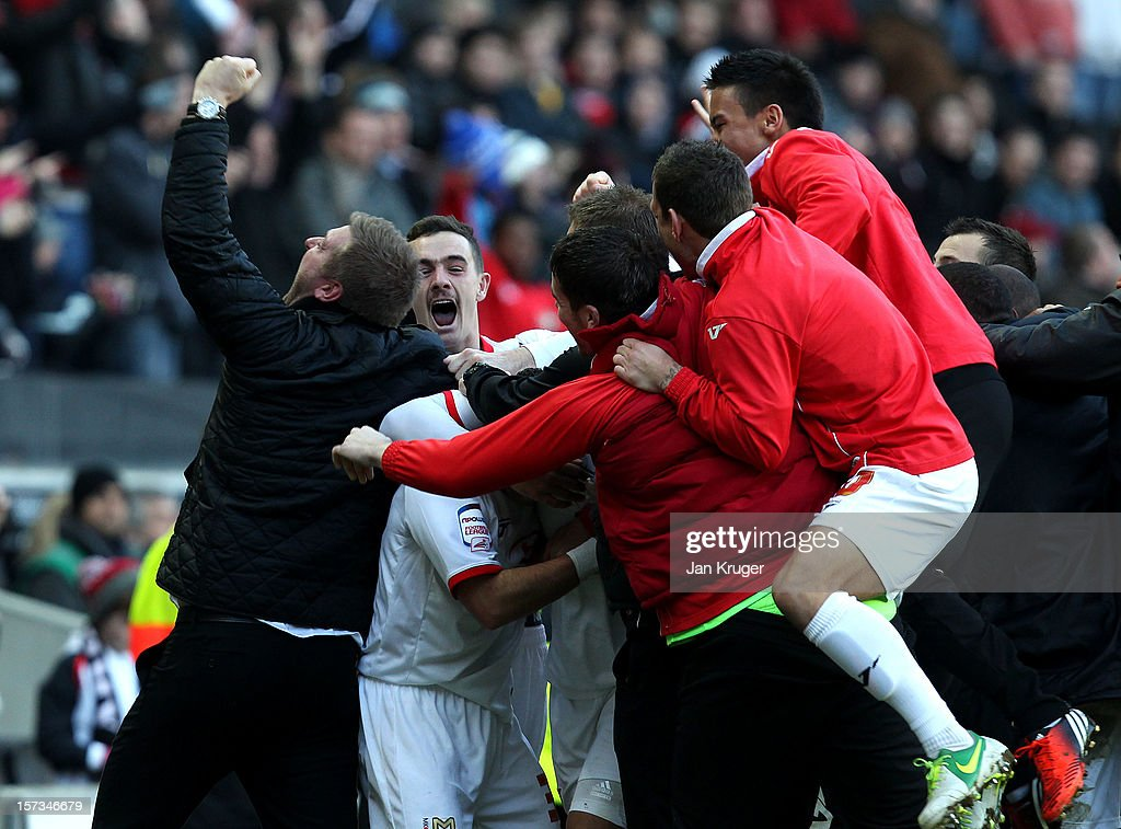 Jon Otsemobor of MK Dons is mobbed by team mates as scores their second goal during the FA Cup with Budweiser Second Round match between MK Dons and AFC Wimbledon at StadiumMK on December 2, 2012 in Milton Keynes, England. This match is the first meeting between the two teams following the formation of AFC Wimbledon (the football club formed in 2002 by supporters unhappy with their club's relocation to Milton Keynes) and the MK Dons (which Wimbledon F.C. controversially became).