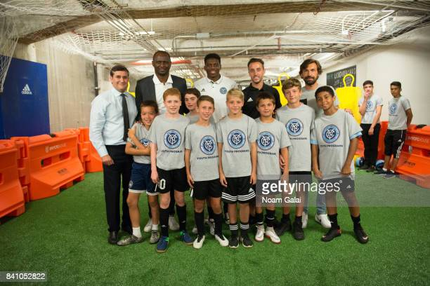 Jon Patricof Patrick Vieira Sean Johnson R J Allen and Andrea Pirlo pose with the kids of the NYCFC Youth Program at the NYCFC popup experience store...