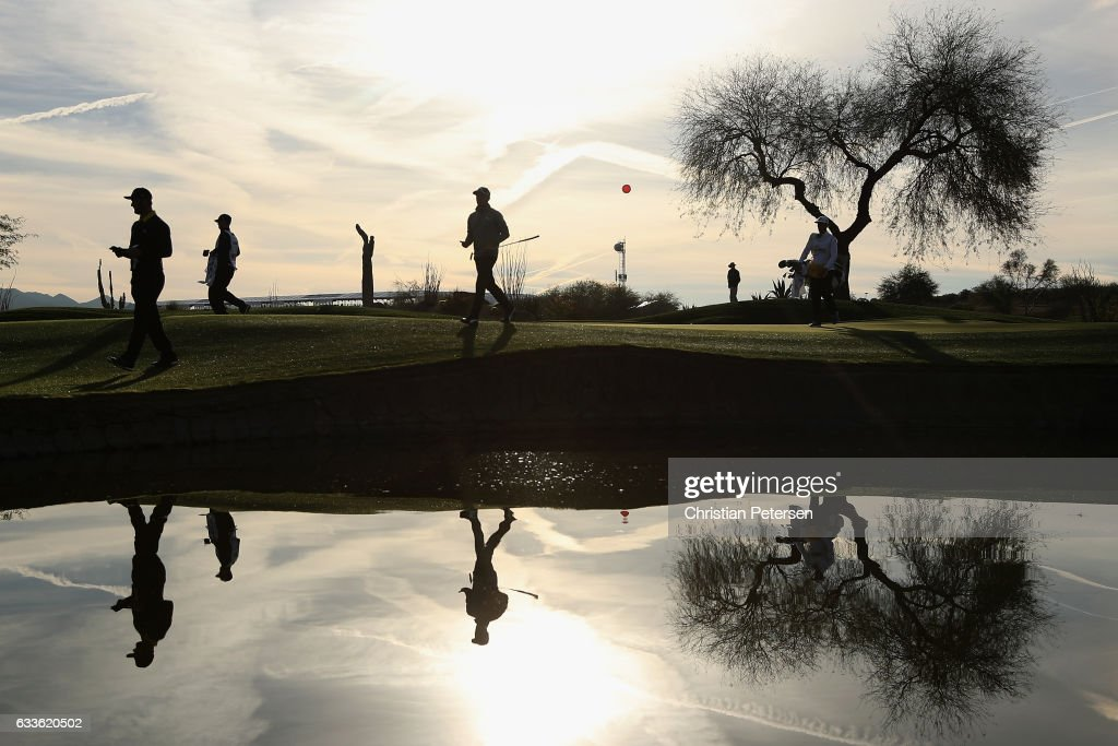 Jon Rahm (L) of Spain and Rickie Fowler (C) walk off the 11th green during the first round of the Waste Management Phoenix Open at TPC Scottsdale on February 2, 2017 in Scottsdale, Arizona.