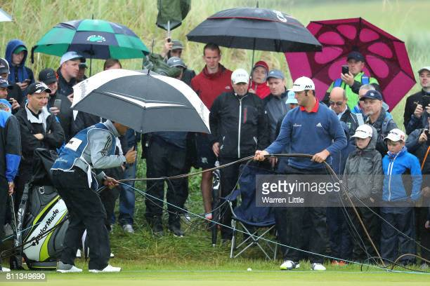 Jon Rahm of Spain moves cables on the 13th hole during the final round of the Dubai Duty Free Irish Open at Portstewart Golf Club on July 9 2017 in...