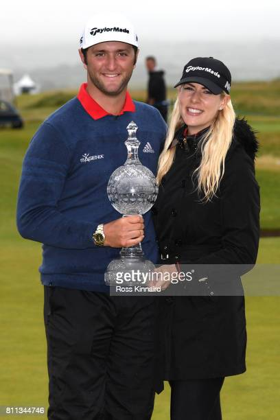 Jon Rahm of Spain poses with the trophy and girlfriend Kelley Cahill after his victory on the 18th hole during the final round of the Dubai Duty Free...