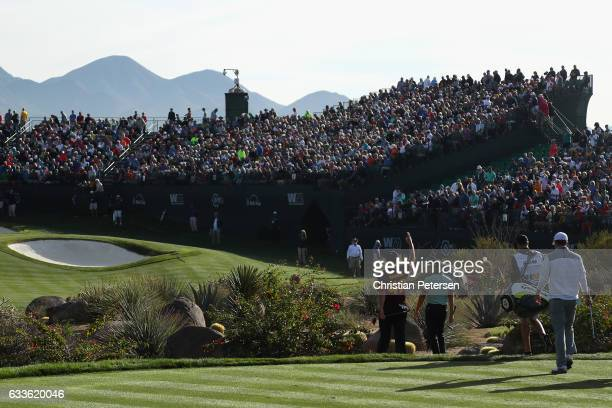 Jon Rahm of Spain Rickie Fowler and Jordan Spieth walk up to the 16th green during the first round of the Waste Management Phoenix Open at TPC...