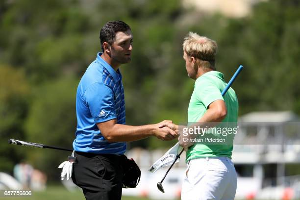 Jon Rahm of Spain shakes hands with Soren Kjeldsen of Denmark after winning their match 75 on the 13th hole during round five of the World Golf...