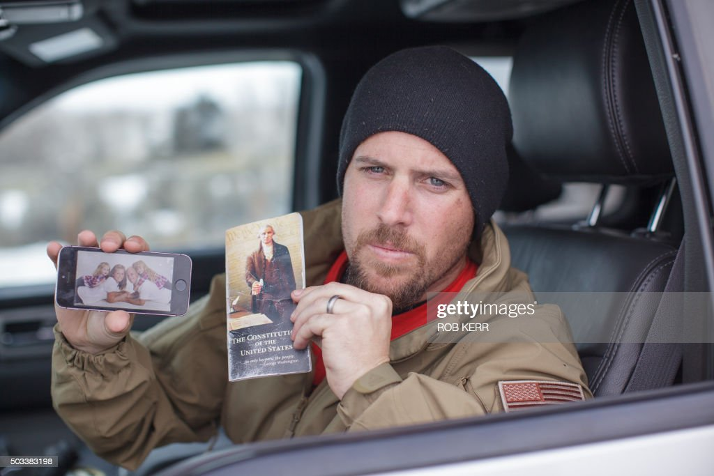 Jon Ritzheimer shows a family picture on his phone and a copy of the US Constitution to the media at the Malheur National Wildlife Refuge...