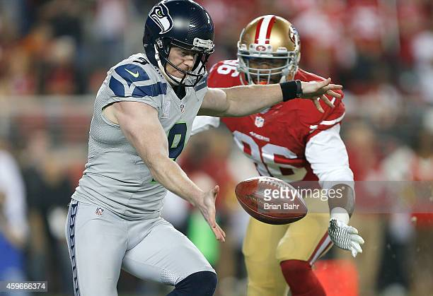 Jon Ryan of the Seattle Seahawks is challenged by Corey Lemonier of the San Francisco 49ers before his punt in the second quarter at Levi's Stadium...