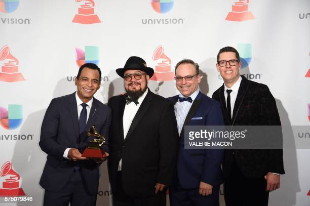 Jon Secada and the Charlie Sepulveda Band pose with the trophy for Best Traditional Tropical Album during the 18th Annual Latin Grammy Awards in Las...