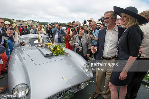 Jon Shirley second right smiles for photographers after his car a 1954 Ferrari 375 MM Scaglietti Coupe was named Best of Show during the 2014 Pebble...