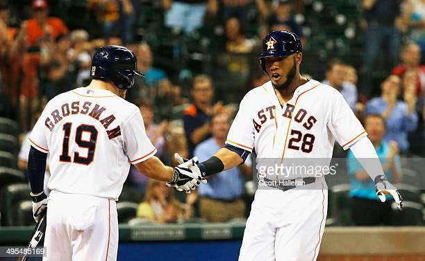 Jon Singleton of the Houston Astros is greeted behind the plate by Robbie Grossman after Singleton hit a solo home run in the eighth inning of their...