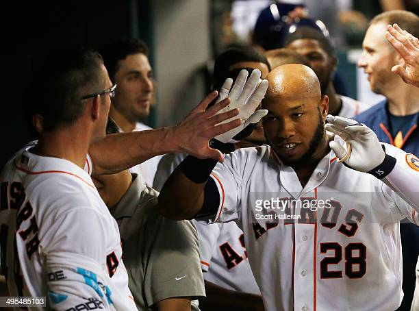 Jon Singleton of the Houston Astros is greeted in the dugout after a solo home run in the eighth inning of their game against the Los Angeles Angels...