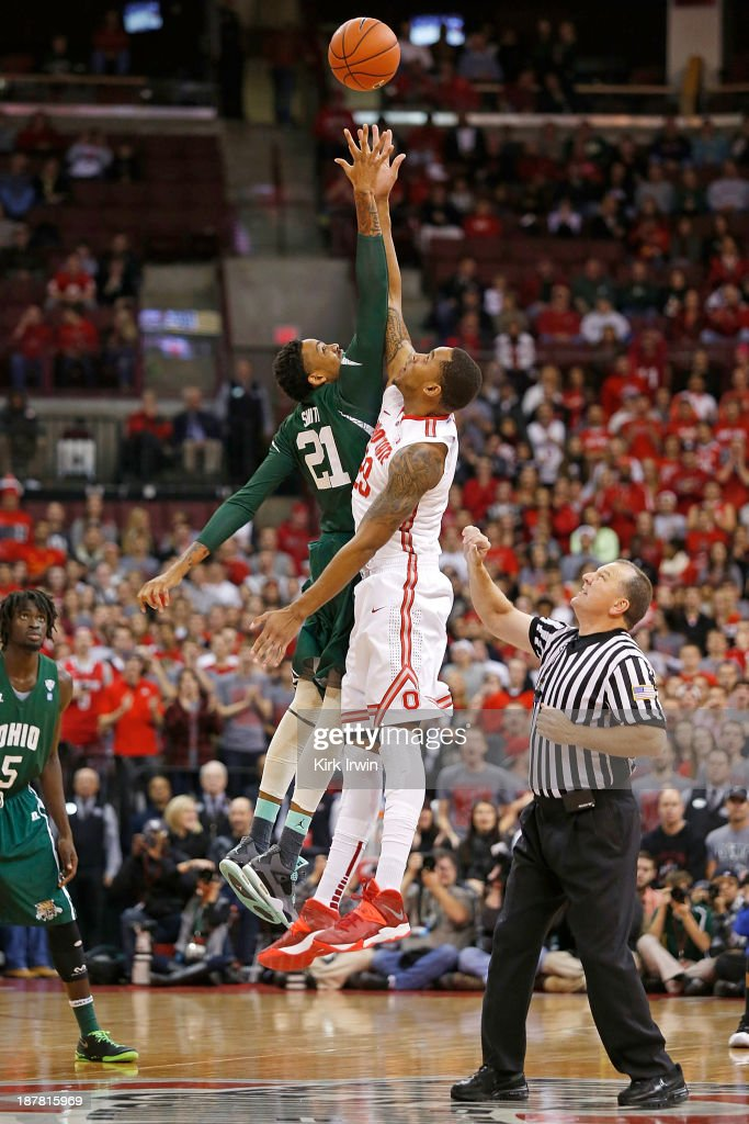 Jon Smith #21 of the Ohio Bobcats and Amir Williams #23 of the Ohio State Buckeyes compete for the tip-off during the first half at Value City Arena on November 12, 2013 in Columbus, Ohio. Ohio State defeated Ohio 79-69.